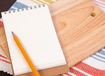 עיפרון, פנקס רשימות וקרש חיתוך על השולחן